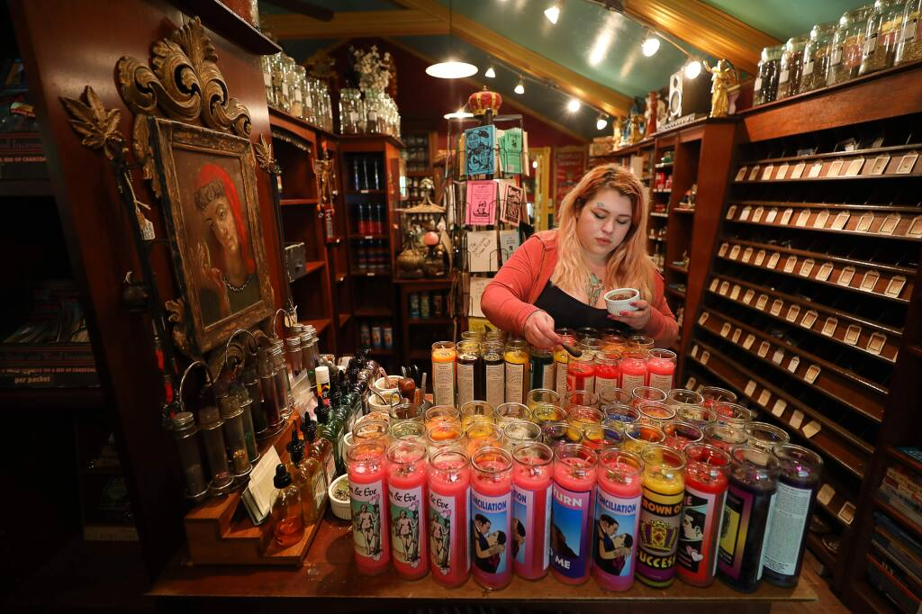 Althea Anderson prepares candles for the altar of the Missionary Independent Spritual Church, at the Lucky Mojo Curio Co. in Forestville on Tuesday, May 21, 2019. (Christopher Chung/ The Press Democrat)
