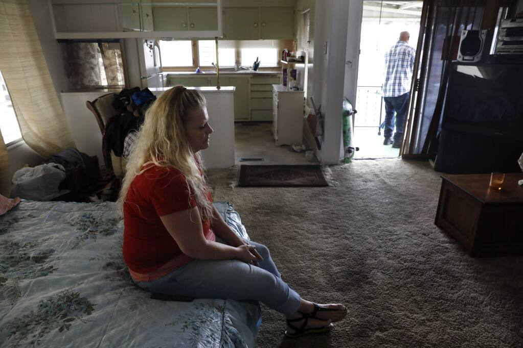 Michelle Trammell sits on her mother's bed inside her home at Journey's End mobile home park in Santa Rosa on Monday, October 1, 2018. (Beth Schlanker/ The Press Democrat)