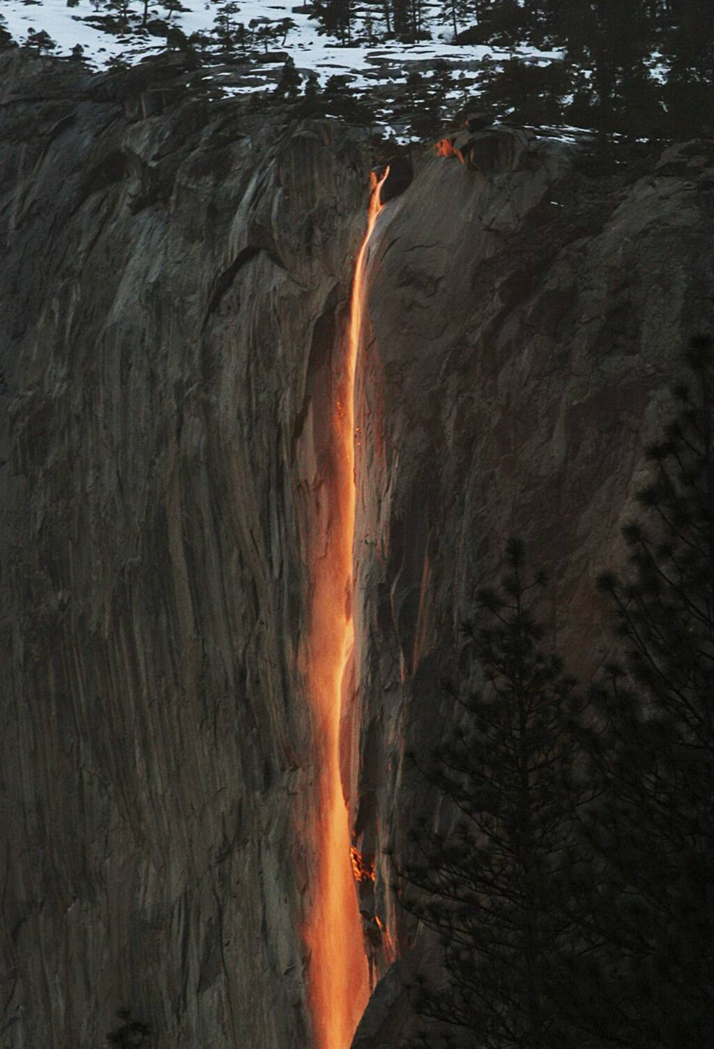 FILE - In this Feb. 16, 2010, file photo, a shaft of sunlight creates a glow near Horsetail Fall, in Yosemite National Park, Calif. Adventurers hoping to see Yosemite National Park's annual 'firefall' will need reservations. At least 50 permits will be issued for each day between Feb. 12 and Feb. 26. The annual event is known to attract over 1,000 sightseers a year. (Eric Paul Zamora/The Fresno Bee via AP, File)