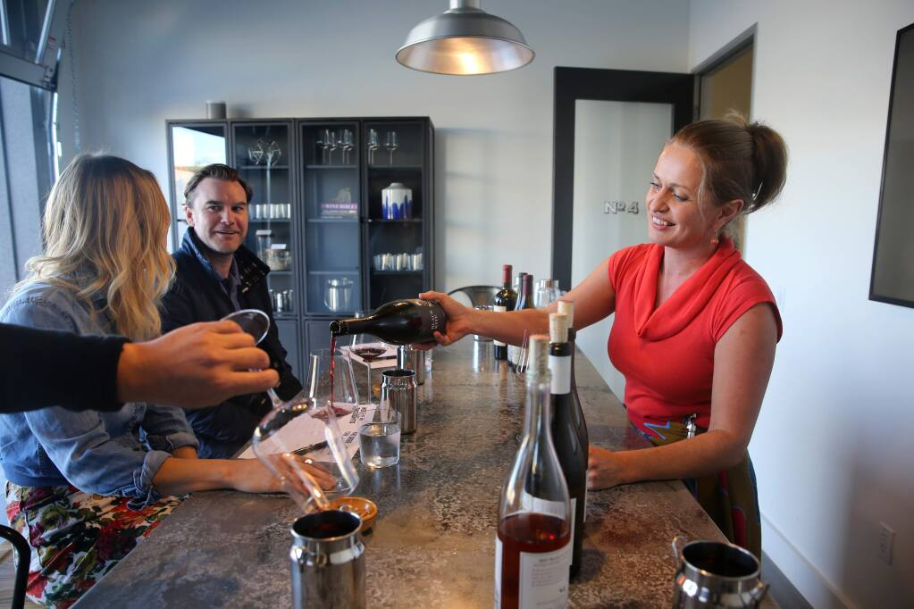 Hospitality manager Nicole Yasinsac, right, pours a glass of Black Kite 2015 Kite's Rest Pinot Noir for guests Katie Fay, left, a hospitality manager at Lambert Bridge Winery, her husband Danny Fay, rear left, a general manager of Kanzler Family Vineyards, and winemaker William Weese, not pictured, during a tasting at Grand Cru Custom Crush in Windsor on Thursday, October 25, 2018. (BETH SCHLANKER/ The Press Democrat)