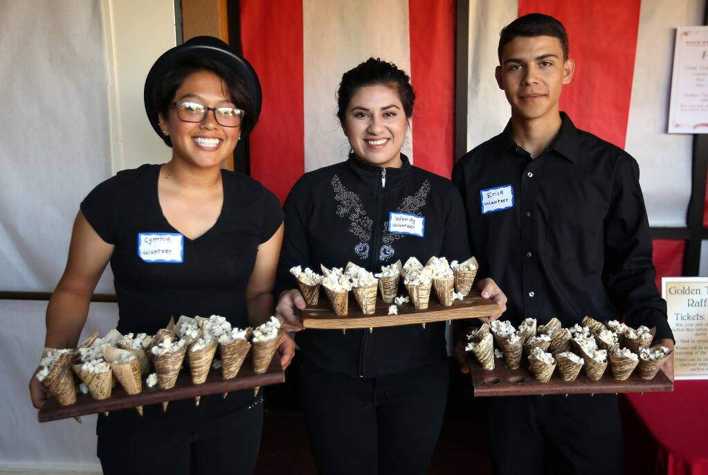 Cynthia Olivares, left, Wendy Ruiz, center and Erick Tinajero all part of Lobo Unity at Elsie Allen, served popcorn to guests who attended the Cirque du SAY fundraiser held at the Friedman Event Center in Santa Rosa, Saturday, April 18, 2015. (Crista Jeremiason / The Press Democrat)