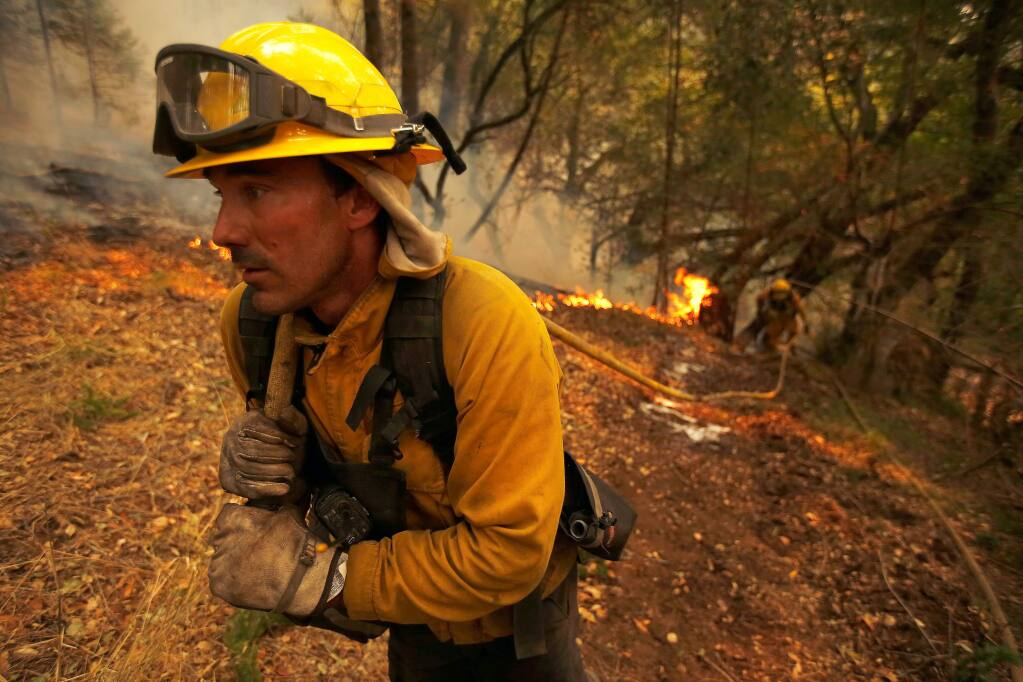 North Lake Tahoe firefighter Julien Lecorps advances a hose lay along a containment line near homes to protect them from the Nuns fire around Hood Mountain Regional Park in Santa Rosa, California on Monday, October 16, 2017. (Alvin Jornada / The Press Democrat)
