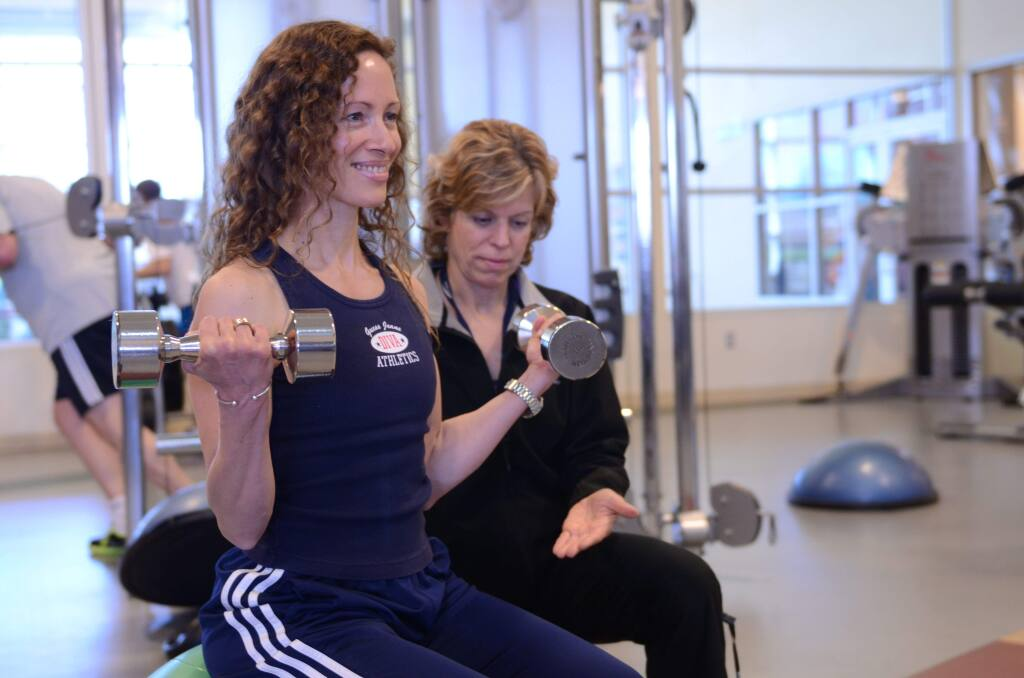 Two St. Joseph Health employees engaged in weight training at the Synergy Medical Fitness Center in the Queen of the Valley Wellness Center in Napa. (Photo courtesy of St. Joseph Health System).