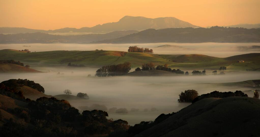 From Wilson Hill Road in Marin County, ground fog hugs Chileno Valley, as the rolling hills of Spring Valley Road, middle, and Mount St. Helena are bathed in morning light, Tuesday, Dec. 24, 2019. (Kent Porter / The Press Democrat) 2019