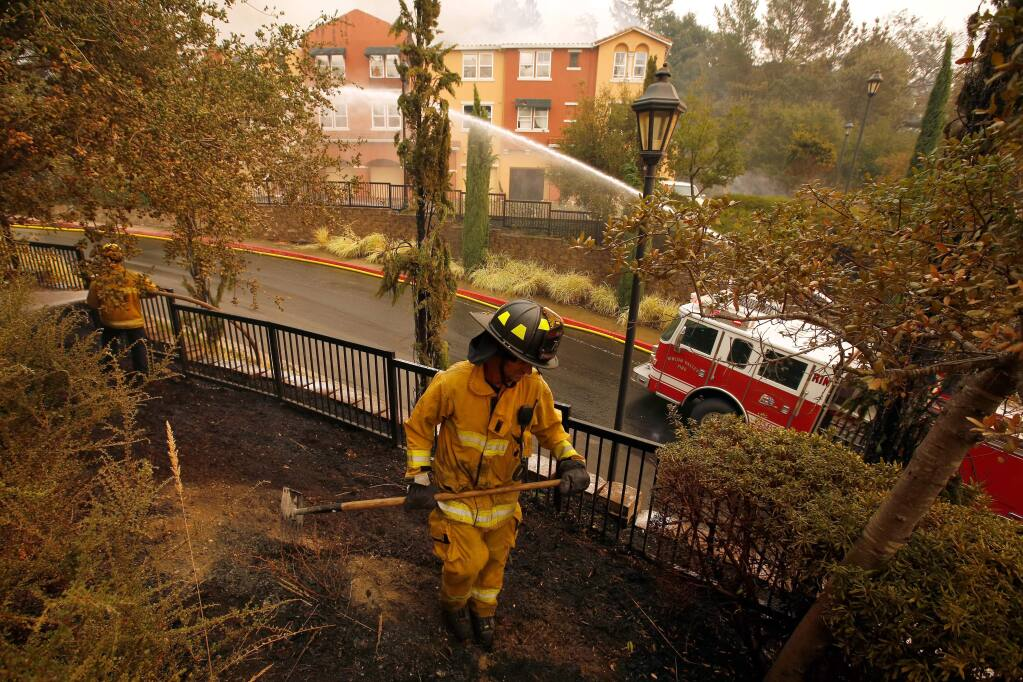 Rincon Valley fire engineer Nate DeJung, center, and other firefighters extinguish fires around The Overlook apartments at Fountaingrove after the Tubbs Fire burned through north Santa Rosa, California on Monday, October 9, 2017. (Alvin Jornada / The Press Democrat)