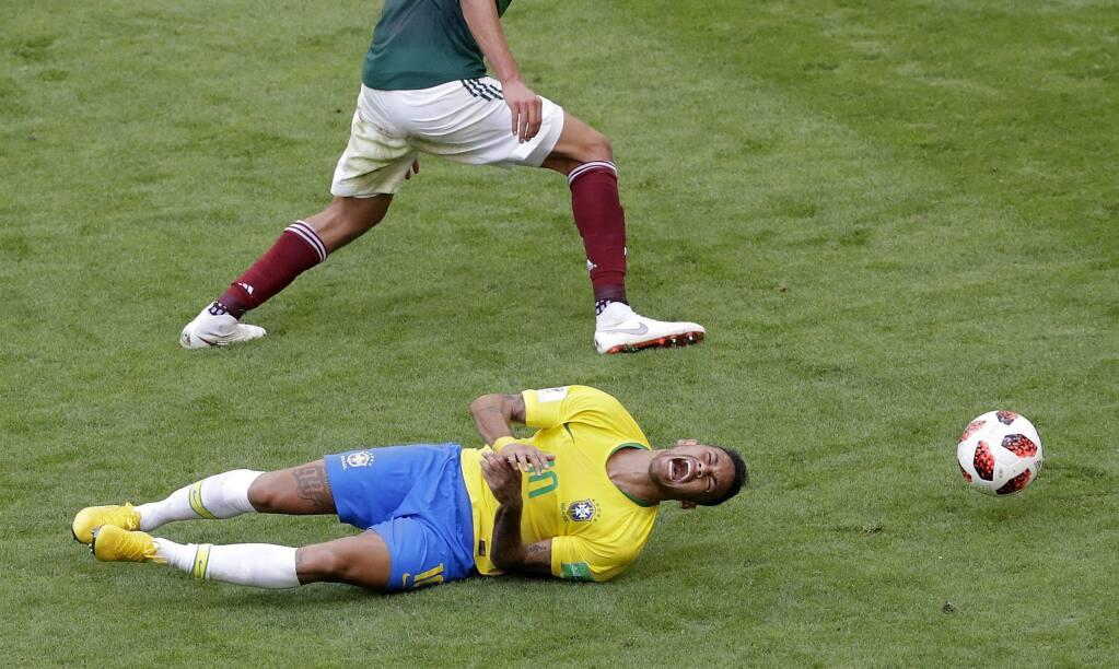 Brazil's Neymar, bottom, lies on the field during the round-of-16 match between Brazil and Mexico at the 2018 soccer World Cup at the Samara Arena, in Samara, Russia, Monday, July 2, 2018. (AP Photo/Sergei Grits)