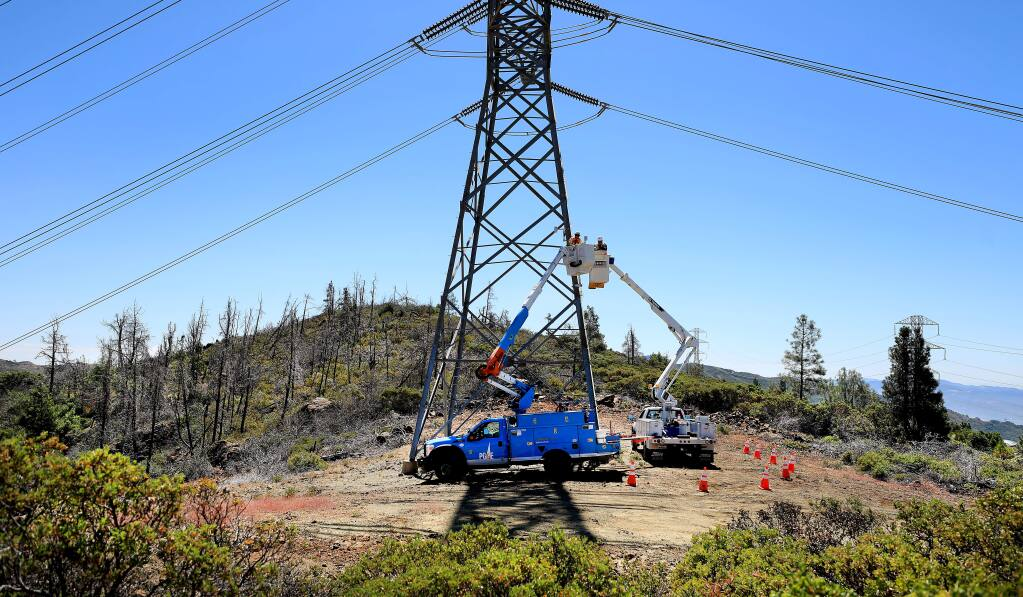 Pacific Gas and Electric communication technicians Andrew Maffei and Mike Fortin install a wireless and solar-powered weather monitoring station on transmission tower above Pine Flat Road in the Mayacamas Mountains of eastern Sonoma County, Tuesday, July 23, 2019. The area has been burned by wildfire several times. (KENT PORTER/ PD)