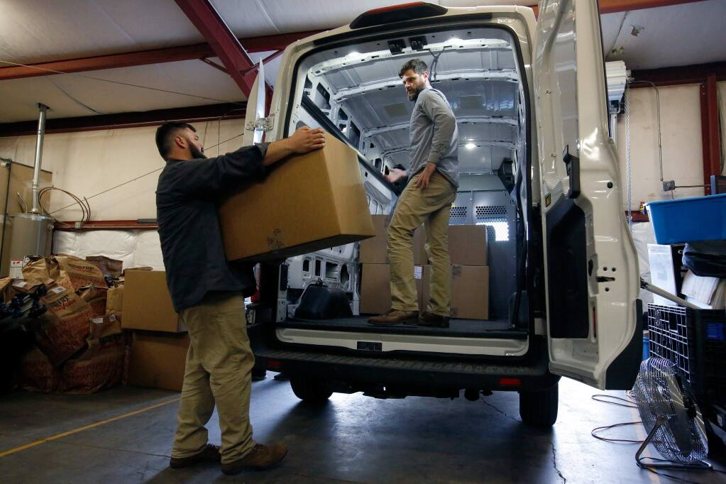 Old Kai Distribution cofounders Matthew Mandelker, left, and Lucas Seymour, who are licensed cannabis distributors, load a delivery van with boxes of their product at their warehouse near Ukiah, California on Tuesday, December 26, 2017. Despite having a Mendocino County cannabis license, a vanload of product from Old Kai Distribution was seized by CHP during a traffic stop of one of their delivery vehicles. (Alvin Jornada / The Press Democrat)