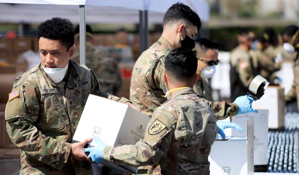 Soldiers with the National Guard pack food boxes at the Redwood Empire Food Bank, Wednesday, April 8, 2020 in Santa Rosa to help with the demand for more food deliveries around the region in response to the coronavirus pandemic. (Kent Porter / The Press Democrat) 2020