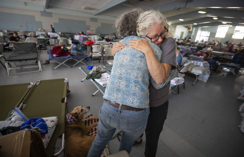 Red Cross volunteer Barbara Wood gives a hug to a Kincade fire evacuee who seemed in distress at the Red Cross shelter at the Sonoma County Fairgrounds on Sunday, Oct. 27, 2019. (JOHN BURGESS/ PD)