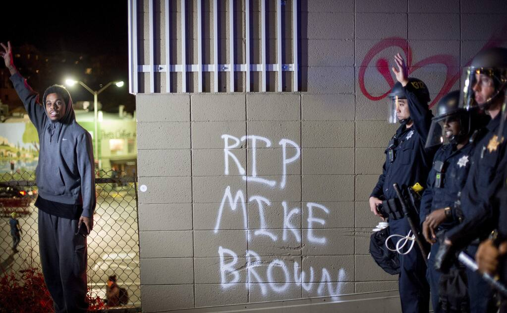 A protester stands near a wall with a graffiti and police officers in Oakland, Calif., on Monday, Nov. 24, 2014, after the announcement that a grand jury decided not to indict Ferguson police officer Darren Wilson in the fatal shooting of Michael Brown, an unarmed 18-year-old. Several thousand protesters marched through Oakland with some shutting down freeways, looting, burning garbage and smashing windows. (AP Photo/Noah Berger)