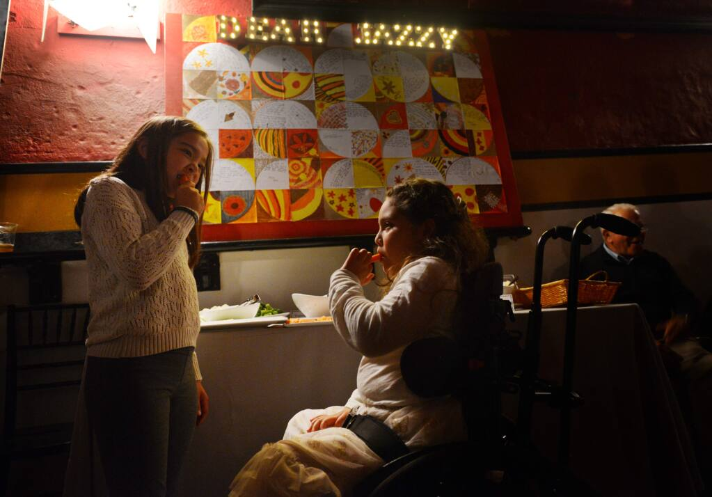 Jazzlin Mejia, 8, right, nibbling on carrots with her best friend Lila Seufert, 8, during Dear Jazzy, a benefit held at the Mystic Theater in Petaluma, California for Jazzlin Mejia who was paralyzed in 2013 when a drunk driver crashed into the car which she and her father were riding. November 20, 2016.(Photo: Erik Castro/for The Press Democrat)