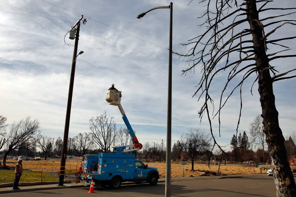 PG&E foreman Freddy Garcia and preapprentice lineman Quienton Smith, lower left, finish installing a temporary streetlight, across the street from a fire-damaged streetlight and burned tree on Jean Marie Drive in the Mark West Estates neighborhood of Santa Rosa, California on Saturday, December 30, 2017. (Alvin Jornada / The Press Democrat)