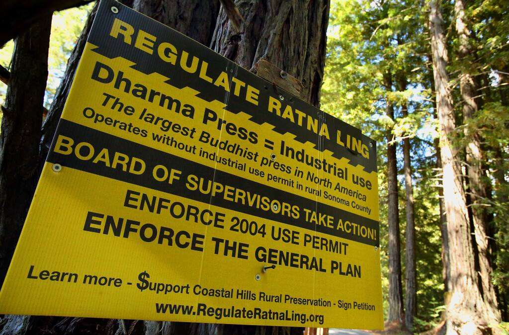 Opponents of Ratna Ling's publishing operation posted signs in the Cazadero area opposing the Buddhist retreat's publishing facility. (Christopher Chung/ The Press Democrat)
