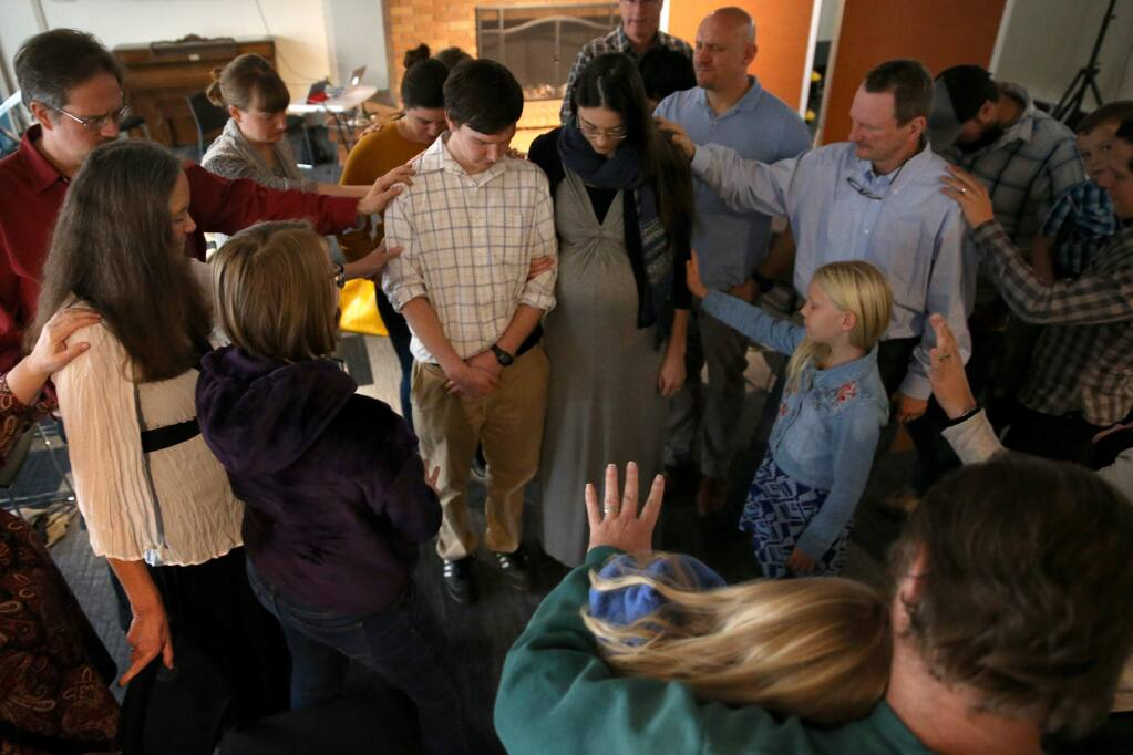 Members of City Alliance Church gather around Jane and Micah Laremore to pray for them before the couple moves to Tyrone, Penn. Photo taken during a worship service held at the Steele Lane Community Center in Santa Rosa on Sunday, November 18, 2018. (BETH SCHLANKER/ The Press Democrat)