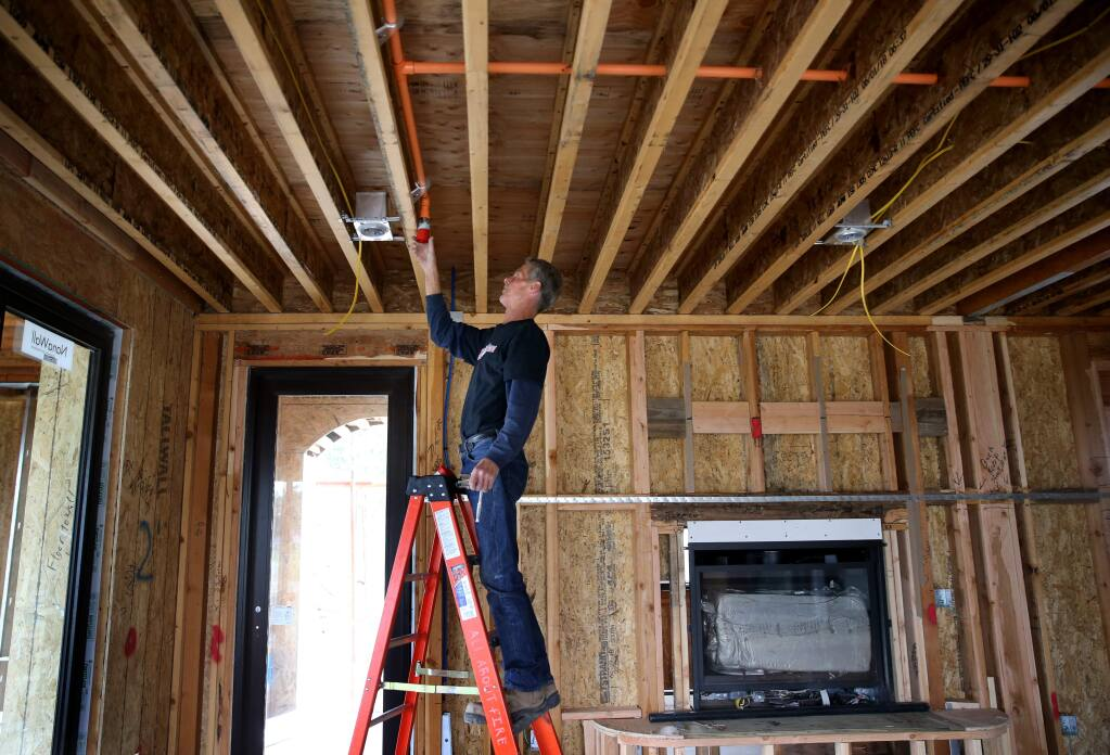Earl Amos, an employee of All About Fire Protection, installs sprinkler heads in a Fountaingrove area home under construction in Santa Rosa on Tuesday, May 14, 2019. (BETH SCHLANKER/ PD)