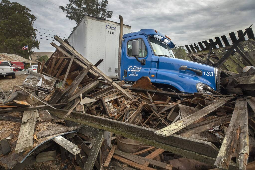 A big rig and two cars collided on Lakeville Highway early Tuesday afternoon. The big rig ended up on top of a fallen down barn across from Ernie's Tin Bar. (photo by John Burgess/The Press Democrat)