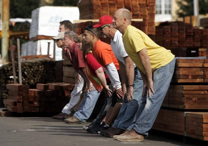 secondary/2 of 2__Construction workers and employees of Central Valley Builders Supply in St. Helena use a stack of lumber for balance as they stretch their backs in a yoga class taught by Allan Nett on Friday, March 30, 2007.photo by John Burgess/The Press Democrat