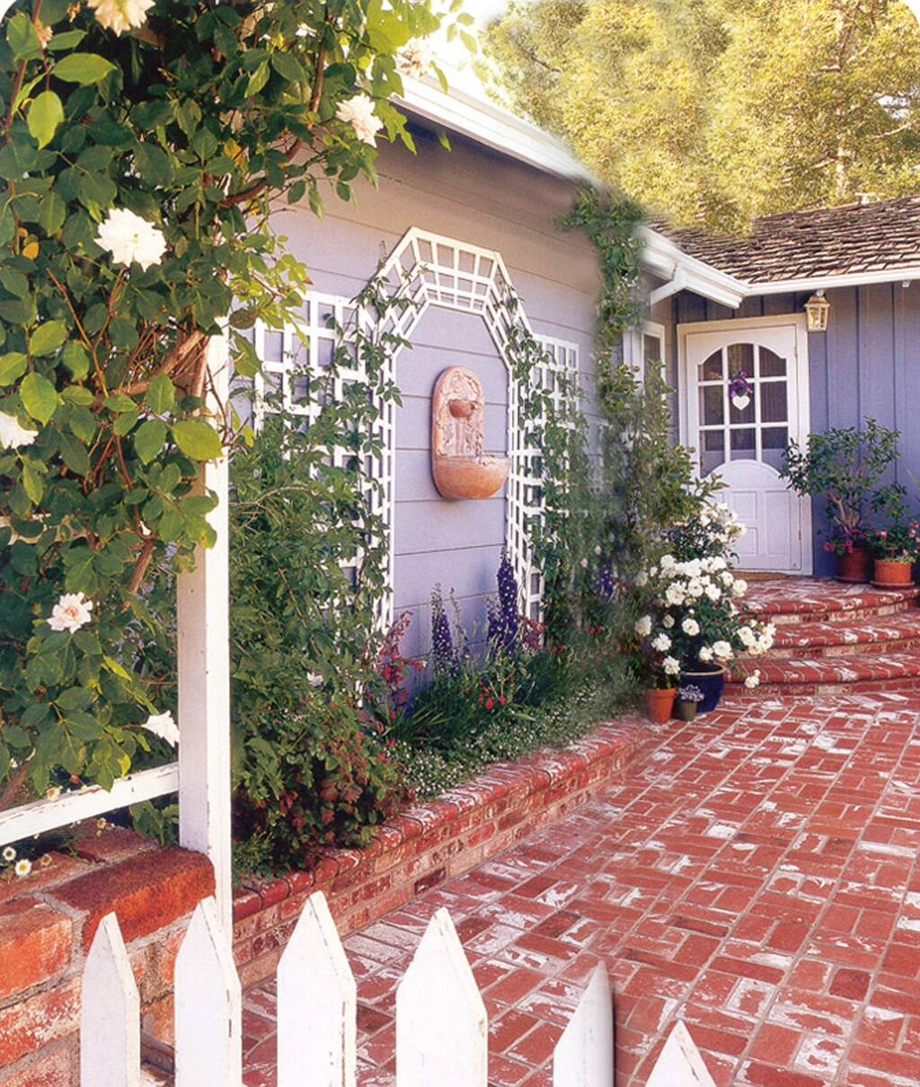 """This home's entrance was transformed from a boring, unadorned walk into an interesting garden by adding wall decorations to the side of the house .Borrowed from the French, this trellising technique called """"tromp l'oeli"""" (meaning 'fool the eye') gives the false impression of a larger, three dimensional space. The fountain in the middle as a focal point adds a sweet sound of trickling water and the whole space is soothing and welcoming. (Louise Leff)"""