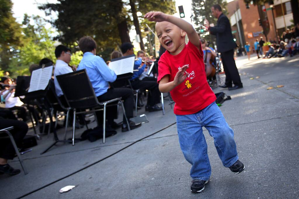 George Barnas, 2, dances to music performed by the Santa Rosa Youth Symphony Repertory Orchestra during the Wednesday Night Market, in downtown Santa Rosa on Wednesday, May 7, 2014. (Christopher Chung/ The Press Democrat)