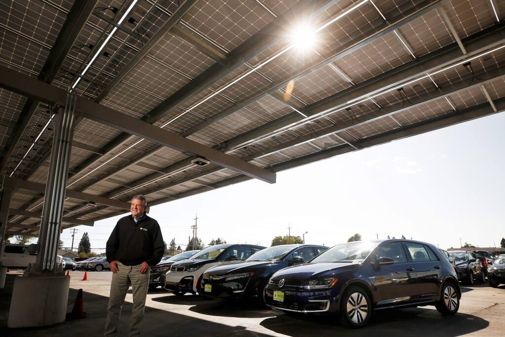 Henry Hansel, president of Hansel Auto Group, poses for a portrait beneath an array of solar panels at Hansel Ford, with a row of various hybrid and electric cars sold by his car dealerships, in Santa Rosa, California, on Thursday, September 19, 2019. (Alvin Jornada / The Press Democrat)