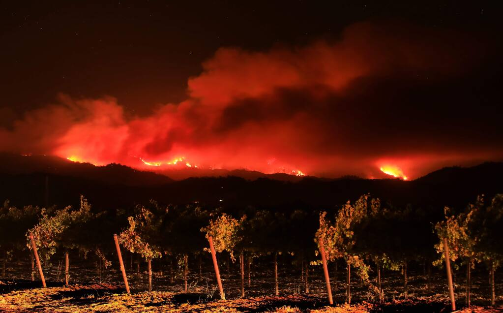 Headlights illuminate a vineyard in the Alexander Valley as the the Kincade fire burns in the Mayacamas Mountains, Friday, Oct. 25, 2019. (Kent Porter / The Press Democrat) 2019