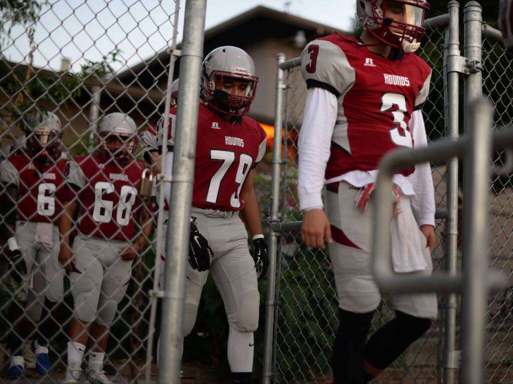 Healdsburg High football players making their way towards the field before the start of a home game against the Harker Eagles, Sept. 15, 2017. (Erik Castro/for The Press Democrat)