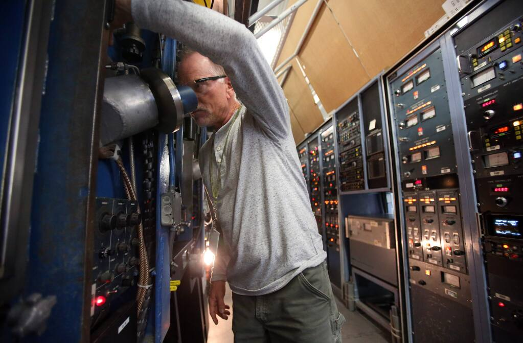 Manufacturing supervisor Michael Biagini monitors sources in the Multilayer Automatic Coater, at MAC Thin Films, Inc., in Santa Rosa on Tuesday, December 2, 2014. (Christopher Chung/ The Press Democrat)