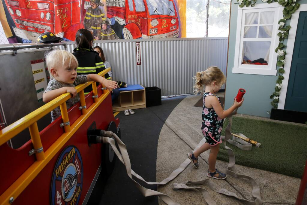 Gregory Webb, 2, left, and his sister Sophia, right, 4, who lost their Coffey Park home in the Tubbs Fire, play in the new Firefighter Playhouse Exhibit at the Children's Museum of Sonoma County in Santa Rosa on Tuesday, June 26, 2018. (Beth Schlanker/ The Press Democrat)
