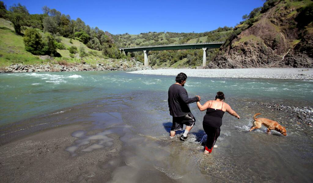 A day of hot weather was enough for Joseph and Rosie Hoaglen of Covelo with their dog dozer to cool off in the middle fork of the Eel River in Dos Rios, Wednesday March 7, 2016. (Kent Porter / Press Democrat) 2016
