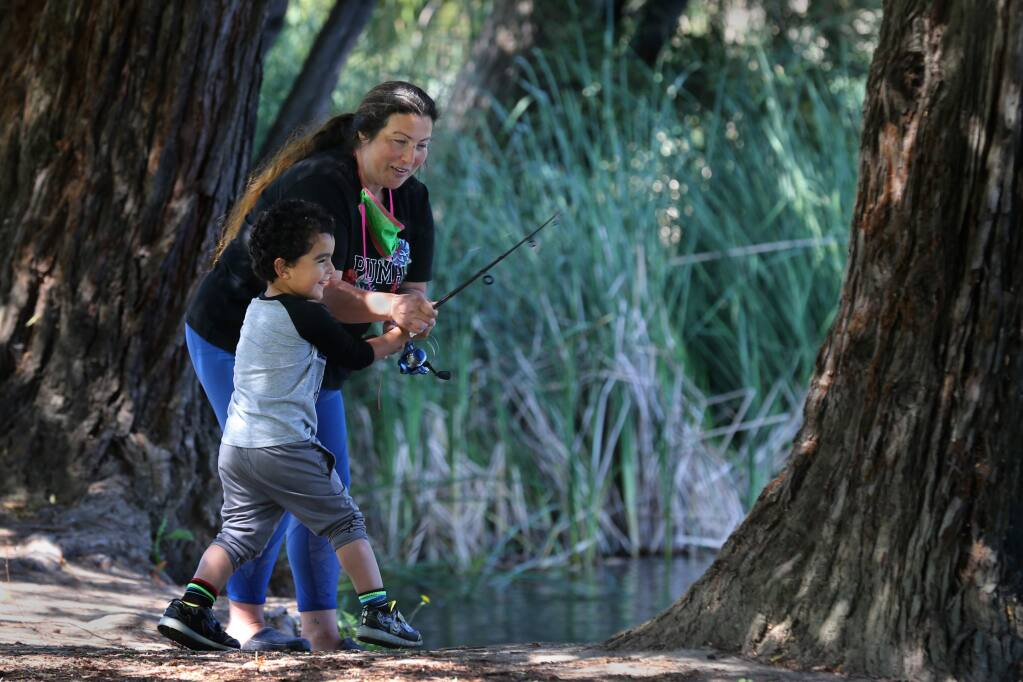 Melinda Hildebrand helps her son, Ronald, 3, cast a fishing line into the water on Mother's Day at Roberts Lake Park in Rohnert Park, California on Sunday, May 10, 2020. (BETH SCHLANKER/ The Press Democrat)