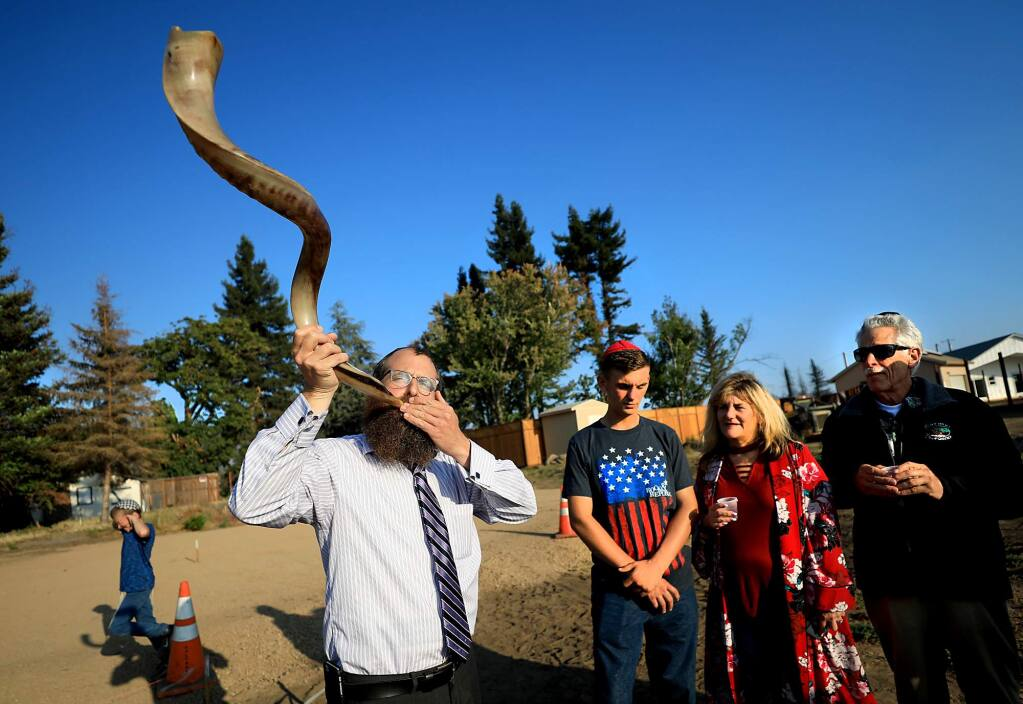 Rabbi Mendel Wolvovsky of Chabad Jewish Center uses a shofar to help bless the rebuilding of a home razed in the Tubbs fire belonging to Barbara Winestock, middle and her son Dylan Chadwick, 19, in Coffey Park, Monday, August 27 in Santa Rosa. At right is congregation member Joseph Wand. (Kent Porter / The Press Democrat) 2018