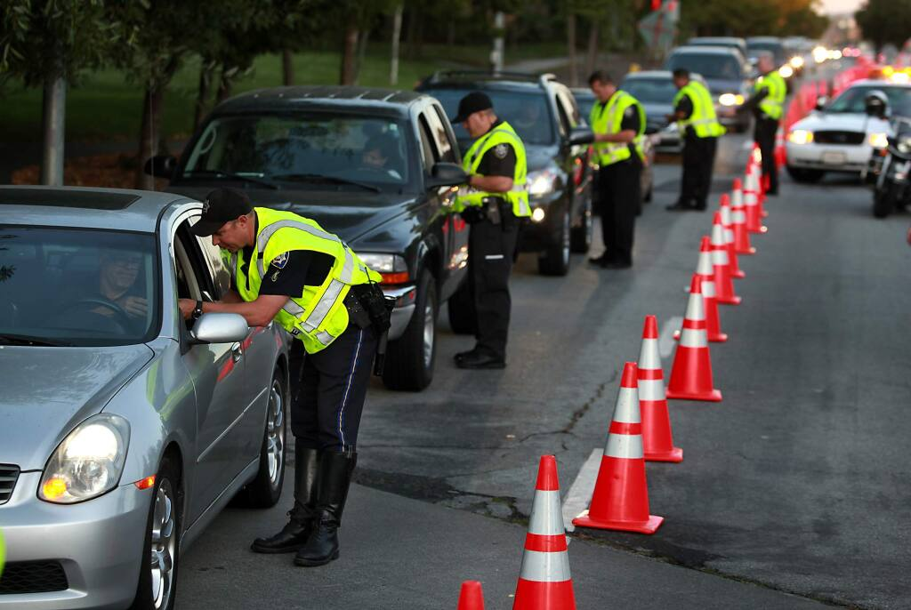 8/1/2010: A1: HIGH-PROFILE CRACKDOWN: Petaluma police officers stop drivers during a recent DUI/driver 's license checkpoint held on Old Redwood Highway.PC: Petaluma police officers stop drivers during a DUI / Drivers License checkpoint held on Old Redwood Highway at North McDowell Extension, Friday, July 23, 2010.