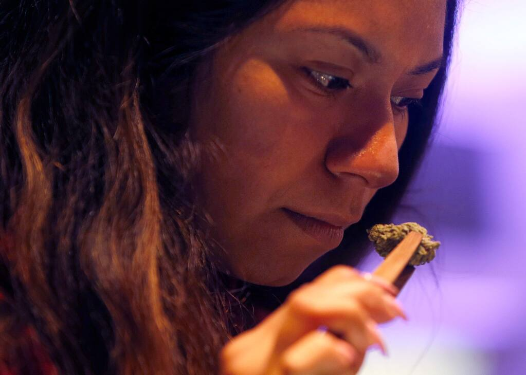 Reyna Herrera of Cloverdale takes in the scent of some marijuana buds at Emerald Pharms cannabis dispensary in Hopland, California, on Thursday, March 1, 2018. (Alvin Jornada / The Press Democrat)