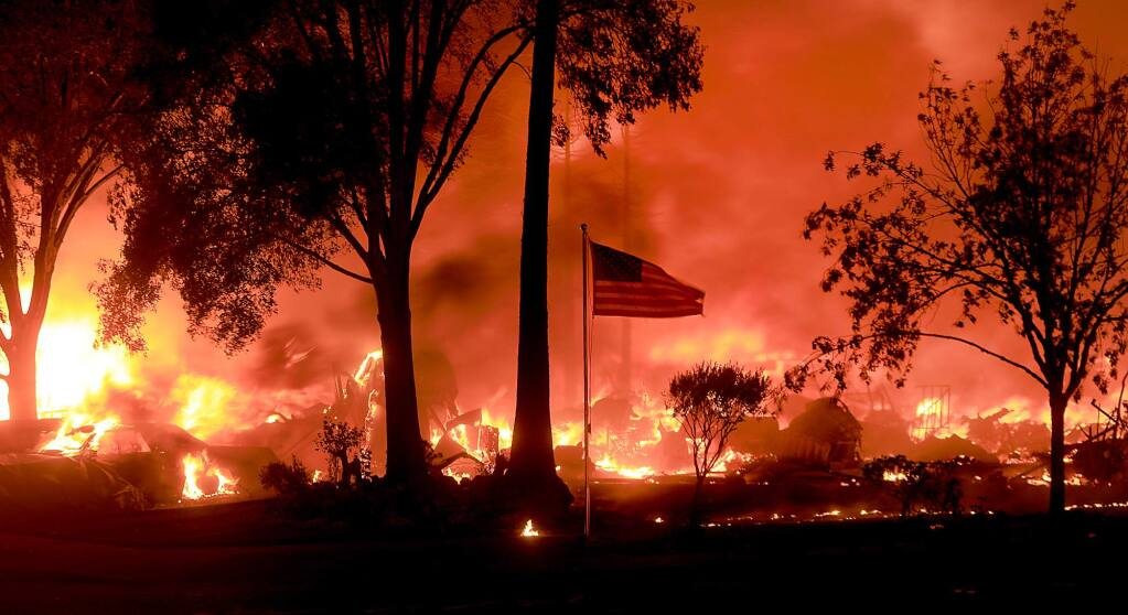 An American flag flies as as structures burn in Coffey Park, Monday Oct. 9, 2017. (Kent Porter / The Press Democrat)