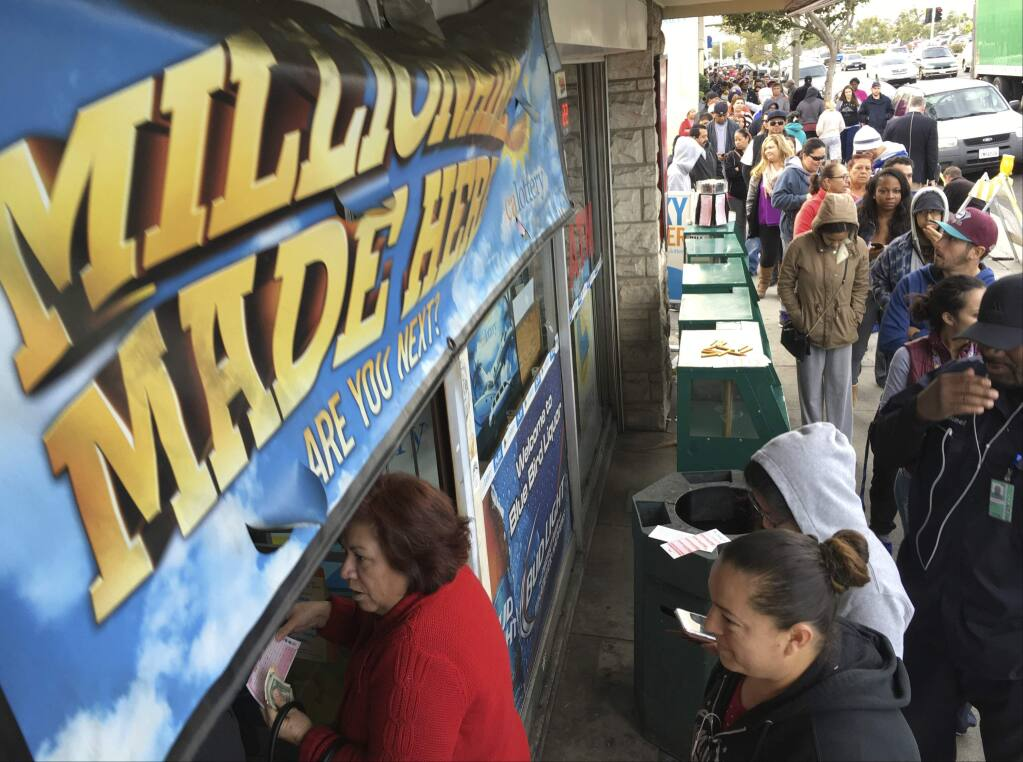 FILE - In this Jan. 13, 2016, file photo, customers wait in line outside the Blue Bird Liquor store to buy Powerball lottery tickets in Hawthorne, Calif. (AP Photo/Damian Dovarganes, File)