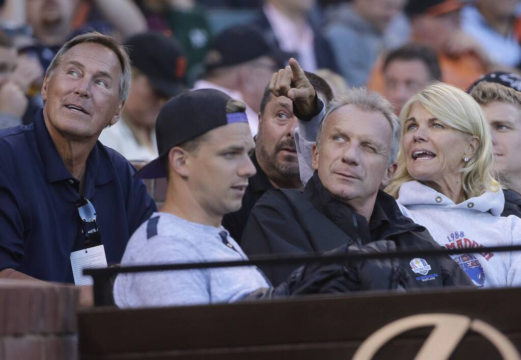Former football player Dwight Clark, left, looks up with Joe Montana, center left, and Montana's wife Jennifer during the third inning of an interleague baseball game between the San Francisco Giants and the Oakland Athletics in San Francisco, Monday, June 27, 2016. (AP Photo/Jeff Chiu)
