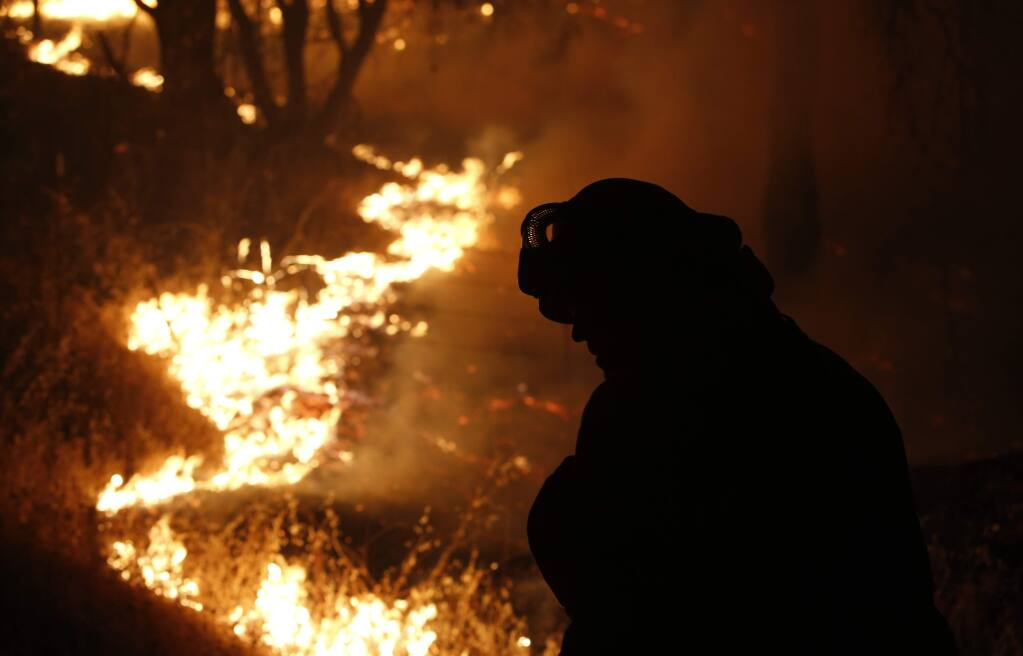 A firefighter turns his head from the flame of the Butte Fire burning near San Andreas, Calif., Friday Sept. 11, 2015.(AP Photo/Rich Pedroncelli)