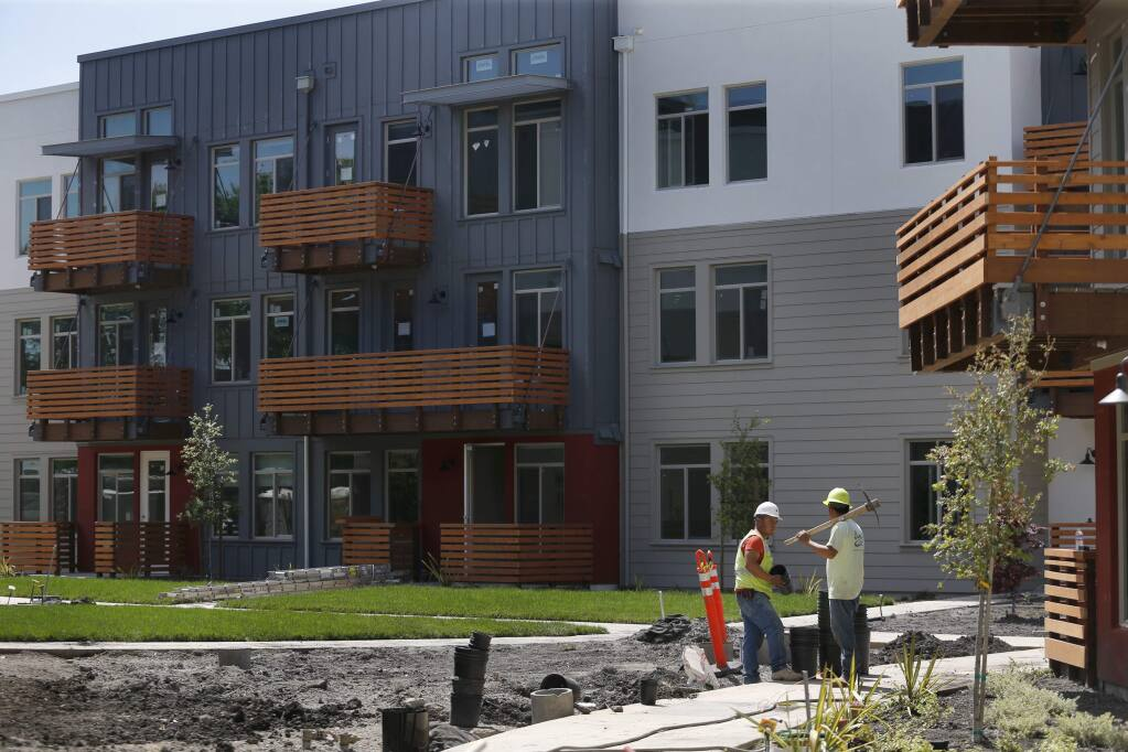 Landscapers work outside new units of the Annadel apartment complex on Monday, April 30, 2018 in Santa Rosa, California . (BETH SCHLANKER/The Press Democrat)