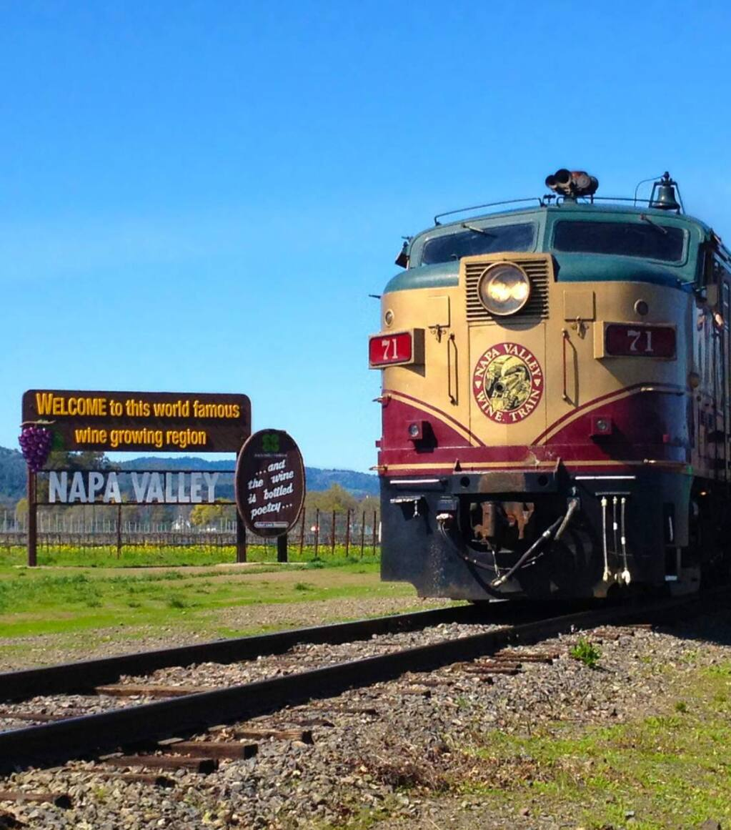 The Wine Train rolls past the Napa Valley welcome sign along Highway 29 north of Yountville in Napa Valley.