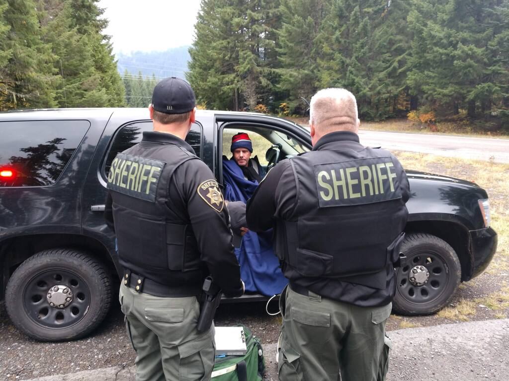 This photo provided by Marion County Sheriff's Office, hiker Robert Campbell sits in a police vehicle after being rescued by the Marion County Sheriff's Office Friday, Oct. 18, 2019, Campbell had been hiking the Pacific Crest Trail and got lost on Thursday in a snowstorm. (Marion County Sheriff's Office via AP)