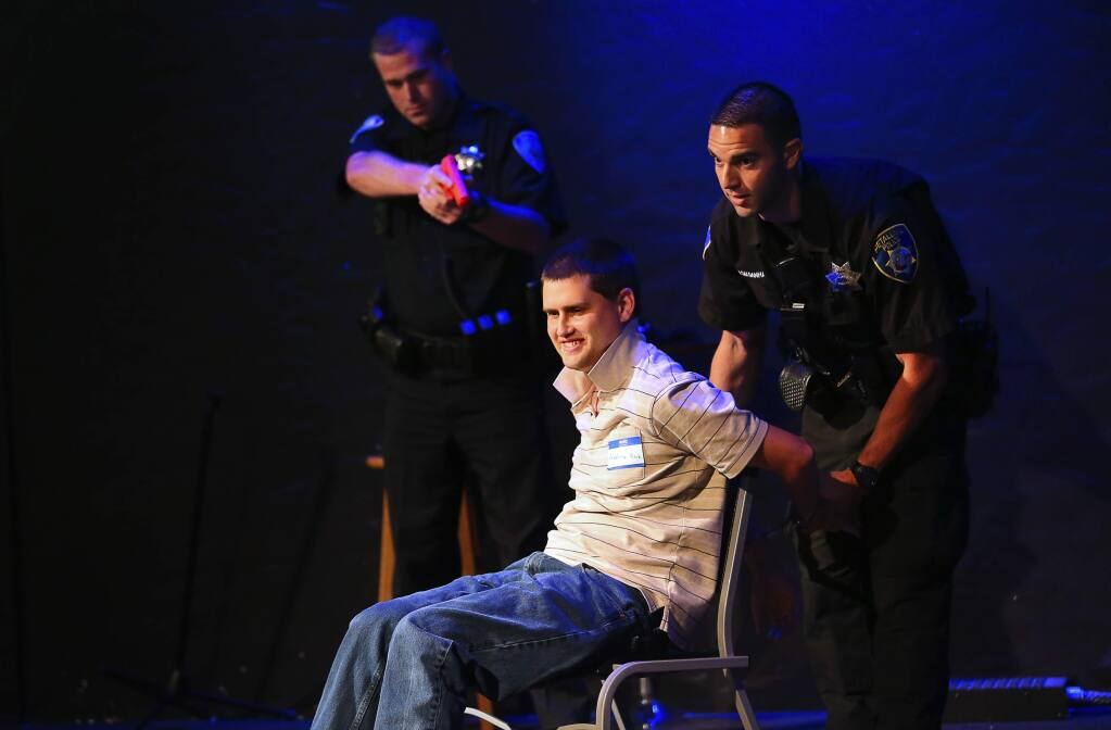 Andrew Kirk, who is autistic, volunteers to show how to comply with police officer commands, as Petaluma Police Officer Tyler Saldanha, right, and Cotati Police Officer Tyler Wardle pretend to arrest him during the Be Safe training program for law enforcement, and individuals with autism spectrum disorders, in Santa Rosa on Thursday, September 21, 2017. (Christopher Chung/ The Press Democrat)