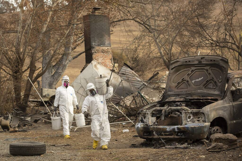 Workers in hazmat suits search for hazardous materials in the ash of the former LaFranchi family home on their Oak Ridge Angus farm on Hwy 128. The buildings on the ranch were consumed by the Kincade fire. (photo by John Burgess/The Press Democrat)