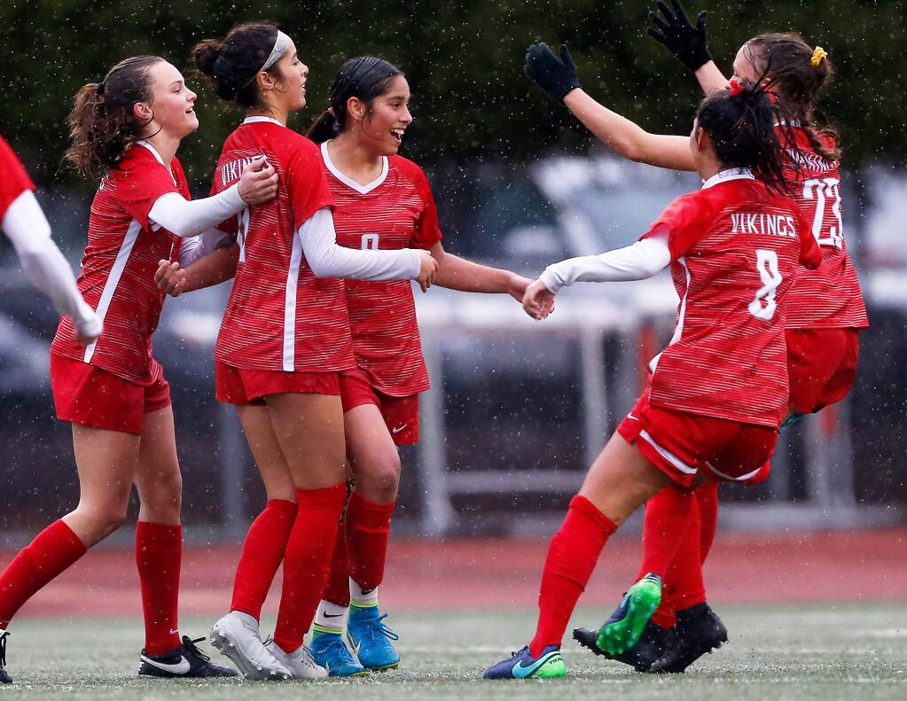 Montgomery's Angelica Barragan (9), center, celebrates with teammates Kaila Watkin (5), left, Kathy Monroy (11), Micky Rosenbaum (8), and Abria Brooker (23) after she scored the Vikings' first goal during the first half of the CIF NorCal regional girls varsity soccer tournament game between Menlo and Montgomery high schools, in Santa Rosa on Tuesday, February 26, 2019. (Alvin Jornada / The Press Democrat)