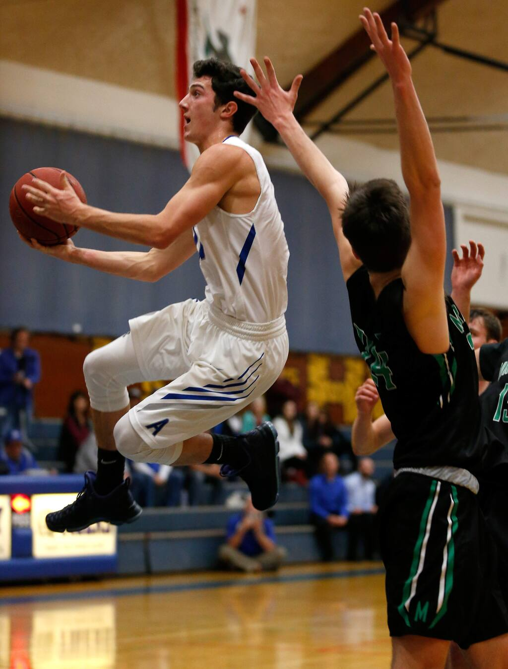 Analy's Dom Tripodi (11), left, leaps past Miramonte's Charlie Hocking (24) to score with a layup during the first half of the NCS Division 2 boys varsity basketball quarterfinal game between Miramonte and Analy high schools in Sebastopol, California on Friday, February 24, 2017. (Alvin Jornada / The Press Democrat)