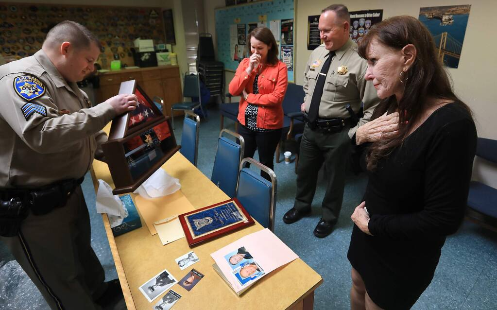 Judy Morris, right, and her son, Marin County sheriff's deputy Robert Heilman and her daughter McKenzie Crownover react as California Highway Patrol Sgt. and family friend Ryan Snider, presents the family with a shadow box containing a CHP badge, American flag, and sergeant stripes to replace what Morris lost in the Tubbs fire belonging to her deceased husband Terrell Morris, Thursday May 3, 2018 at the CHP office in Rohnert Park. (Kent Porter / The Press Democrat) 2018