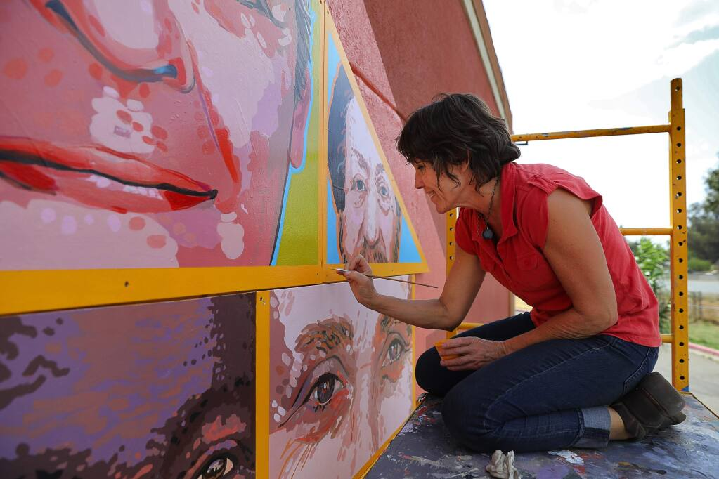 Artist Jennifer Tatum touches up the Palms Inn Project in Santa Rosa on Tuesday, September 12, 2017. (Christopher Chung/ The Press Democrat)