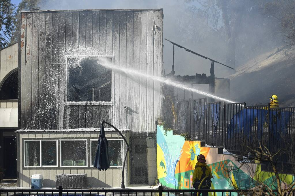 Firefighters shoot water at the Lafayette Tennis Club building in Lafayette, Calif., on Sunday, Oct. 27, 2019. Crews battled a 6-acre grass fire between Camino Diablo and Springbrook Road near State Route 24. (Jose Carlos Fajardo/Bay Area News Group/San Jose Mercury News via AP)