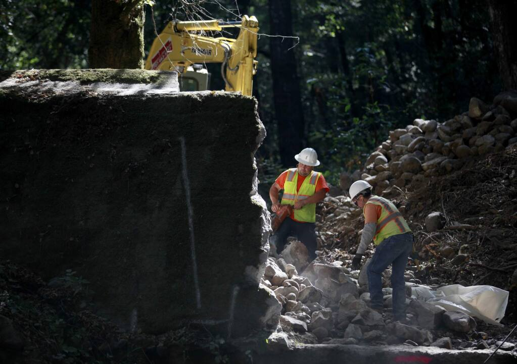 Rafael Cervantes, left, and Fernando Callivillo, employees with Hanford A.R.C., work to demolish the Glenn Oaks flashboard dam as part of the construction of a fish way for steelhead trout on Stuart Creek on Friday, September 12, 2014 in Sonoma, California. (BETH SCHLANKER/ The Press Democrat)