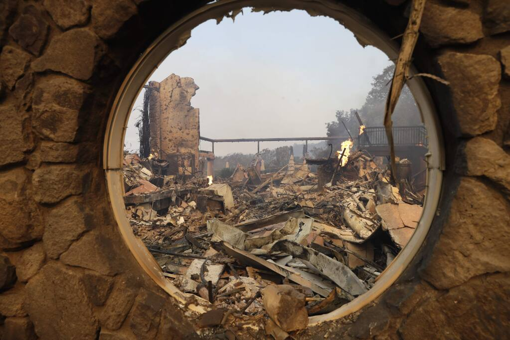 The fire-ravaged Signorello Estate winery is seen through a window Monday, Oct. 9, 2017, in Napa, Calif. Wildfires whipped by powerful winds swept through Northern California sending residents on a headlong flight to safety through smoke and flames as homes burned. (AP Photo/Marcio Jose Sanchez)